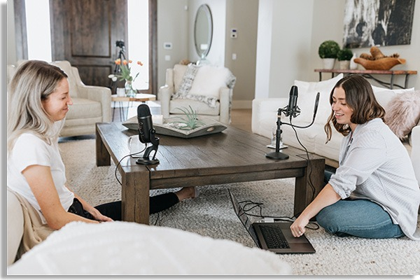 photo of two women sitting on a living room floor, with microphones on a wooden table and a notebook on the floor, as if they were creating podcasts