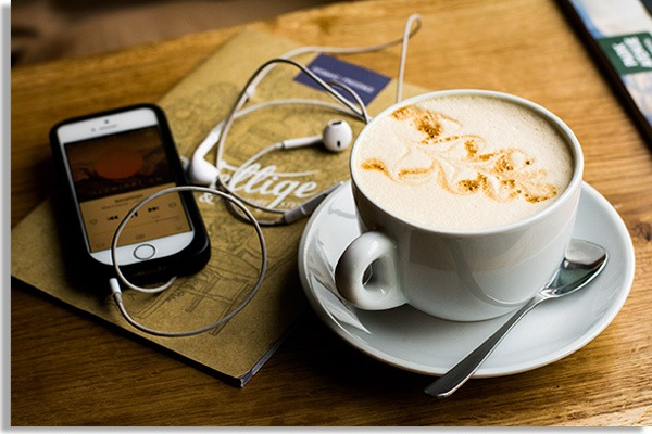 wooden table with teapot, teaspoon and mug filled with coffee with milk. Beside, a cellphone with headphones