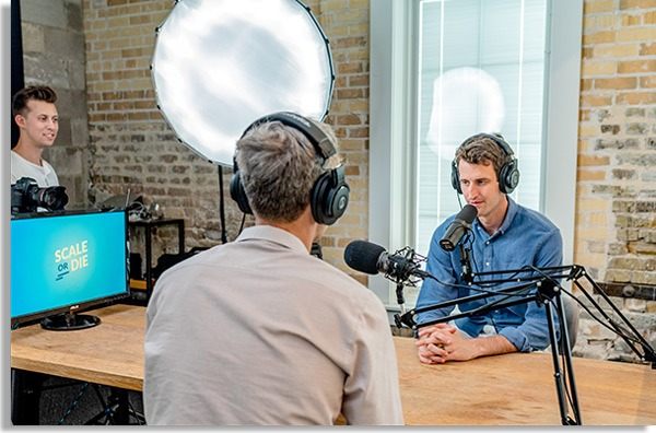 photo of two men talking with headsets and microphone, as if recording podcasts